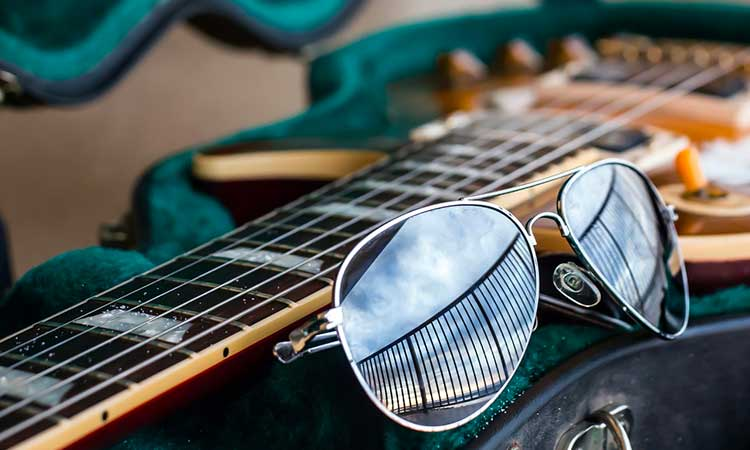 A pair of sunglasses resting against the neck of an electric guitar. The sunglasses reflect the railing of a balcony and a sunrise over the ocean.