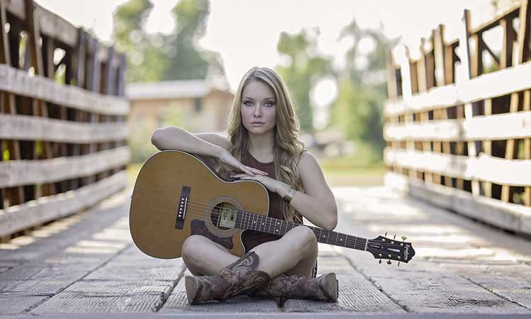 A woman sits cross legged in the middle of a bridge. An acoustic guitar rests in her lap.