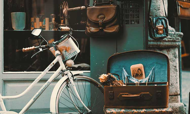 The front of an old corner store. The window displays various trinkets. A bicycle is parked outside. An open suitcase willed with nick-knacks is set on a stool. A few leather bags hang from the wall.