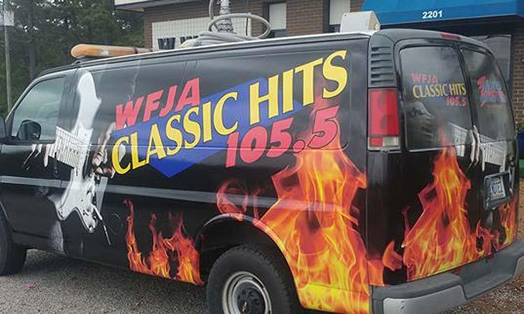 WFJA/WWGP Radio van. A black van featuring WFJA's logo, a guitar being strummed, and flames.