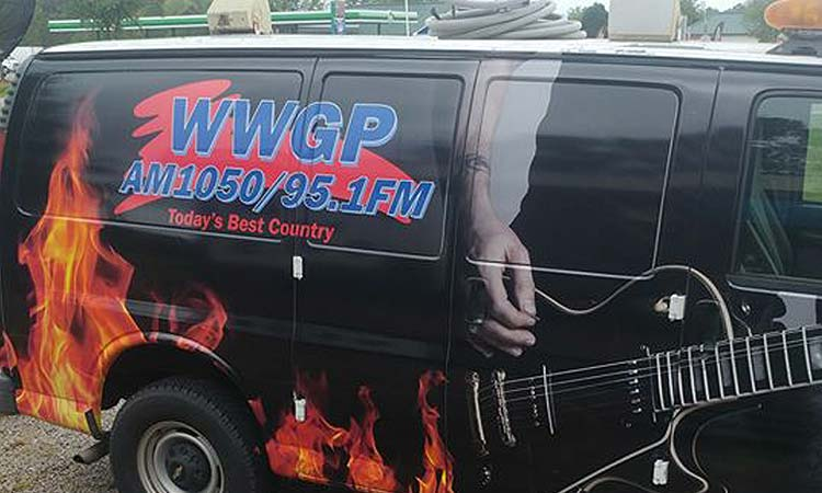 WFJA/WWGP Radio van. A black van featuring WWGP's logo, a guitar being strummed, and flames.