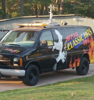 WFJA/WWGP Radio van. A black van featuring WFJA's logo, a guitar being strummed, and flames.