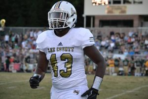 A football player from Lee Senior. His uniform is white with gold lettering and bares the number 43.