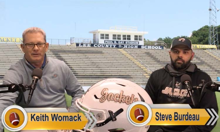 Sports host Keith Womack sits with Coach Burdeau with the Lee County High School football field in the background