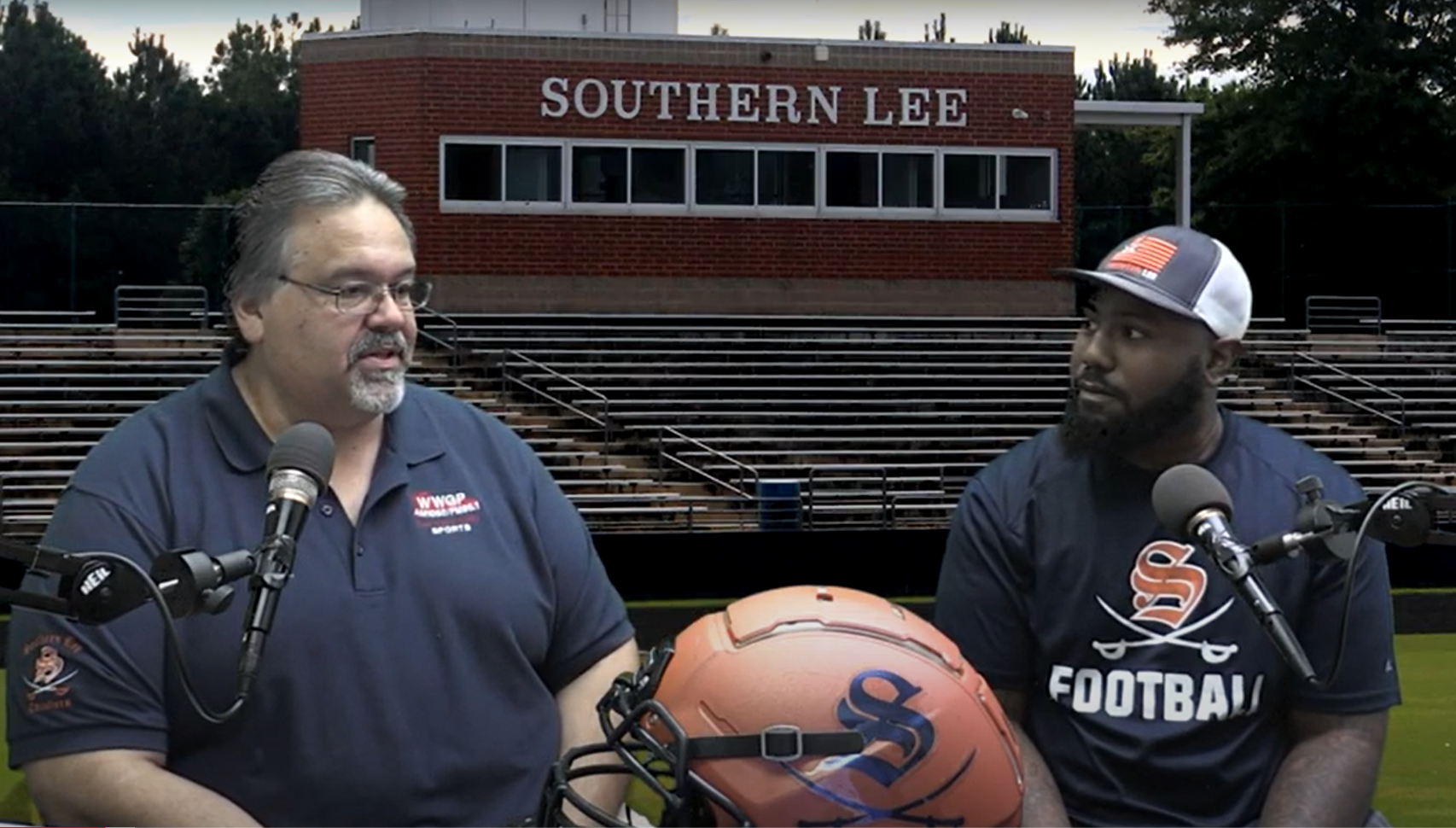 Sports host Mike Fowler sits with Coach McClure with the Southern Lee High School football field in the background