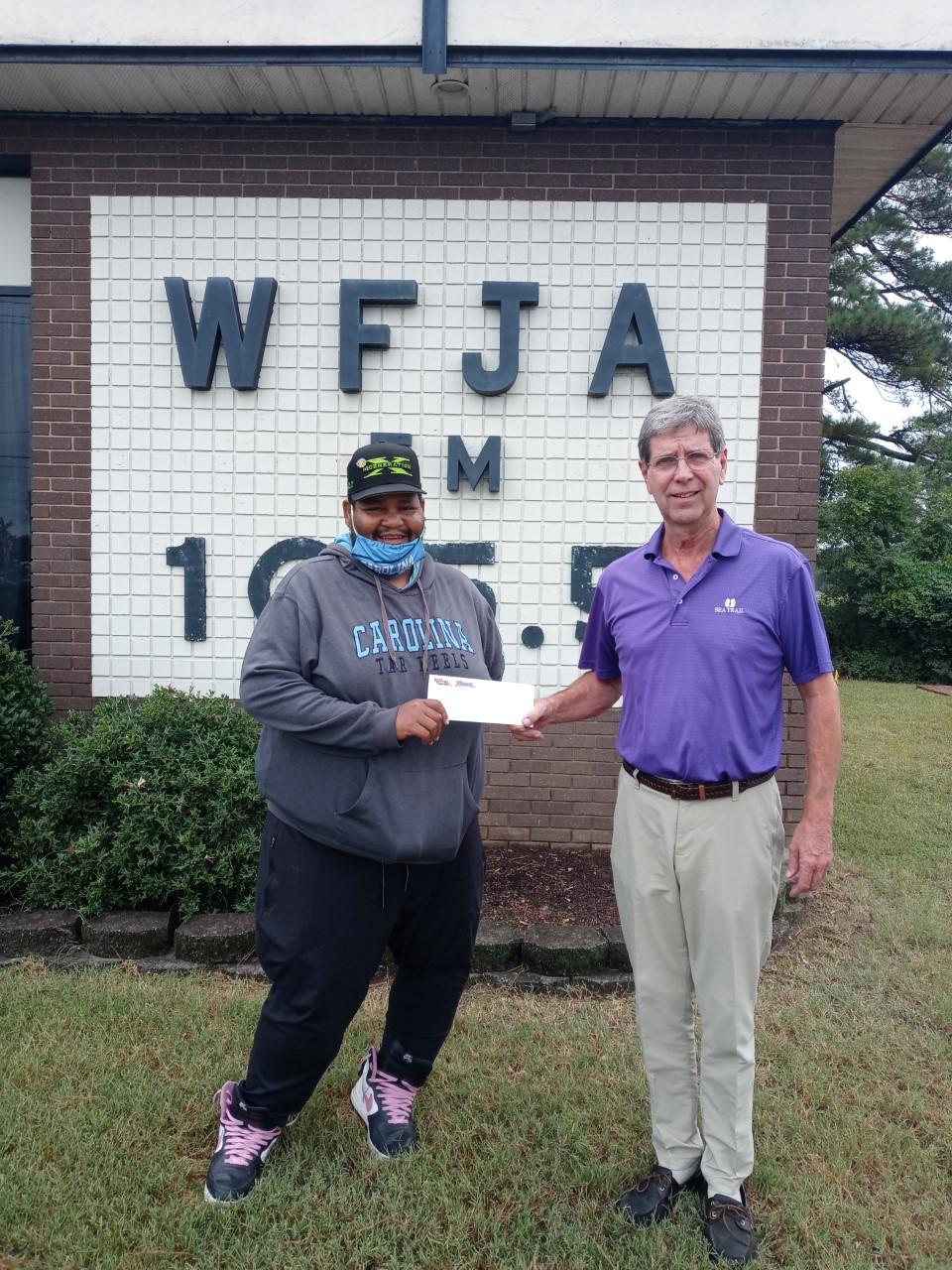 Jon Hockaday, CEO of Sandhills Broadcasting handing prize money to Sanford, North Carolina local, Michael Freeman. Michael Freeman was the 2021 winner of the WFJA Summer Cash Giveaway.