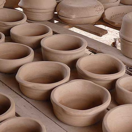 Rows of raw clay dishware ready to be cooked.